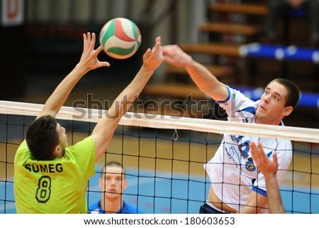 KAPOSVAR, HUNGARY - FEBRUARY 25: Tamas Vajda (white 14) in action at a Hungarian National Championship volleyball game Kaposvar (white) vs. Sumeg (green), February 25, 2014 in Kaposvar, Hungary. - stock photo