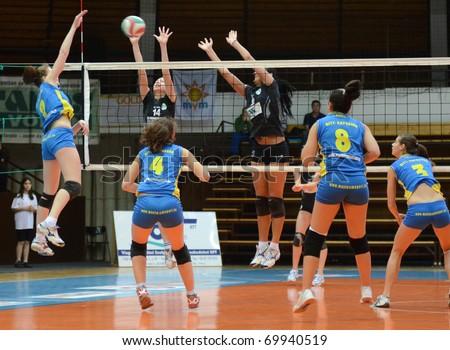 KAPOSVAR, HUNGARY - JANUARY 23: Rebeka Rak (L) strikes the ball at the Hungarian NB I. League woman volleyball game Kaposvar vs Miskolc, January 23, 2011 in Kaposvar, Hungary. - stock photo