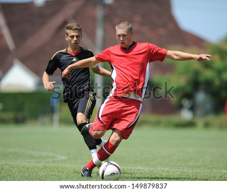KAPOSVAR, HUNGARY - JULY 20: Unidentified players in action at the IX. Youth Football Festival match Nagybajom (red) (HUN) vs. Liceul Sportiv (black) (MDA) on July 20, 2013 in Kaposvar, Hungary - stock photo