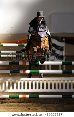 KAPOSVAR, HUNGARY - MARCH 28: An unidentified competitor jumps with his horse on the Masters Tournament International Jumping Competition, March 28, 2010 in Kaposvar, Hungary. - stock photo