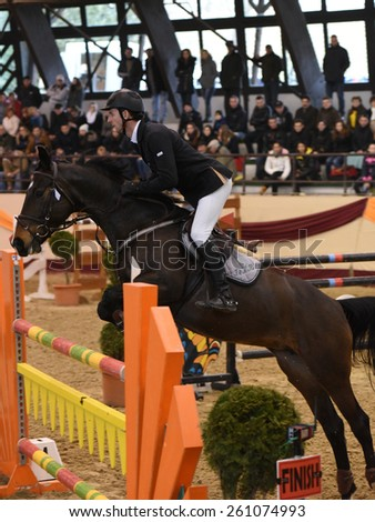 KAPOSVAR, HUNGARY - MARCH 15: Andrija Hrgovic jumps with his horse (Calysta) on the Masters Tournament International Jumping Competition, March 15, 2015 in Kaposvar, Hungary - stock photo