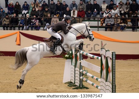 KAPOSVAR, HUNGARY - MARCH 24: Balazs Sandor jumps with his horse (Calossa Hatchee) on the Masters Tournament International Jumping Competition, March 24, 2013 in Kaposvar, Hungary - stock photo