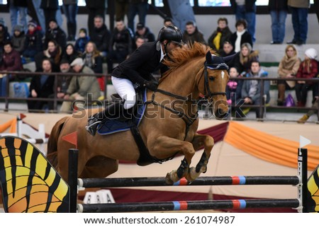 KAPOSVAR, HUNGARY - MARCH 15: Laszlo Gombos jumps with his horse (Eragon) on the Masters Tournament International Jumping Competition, March 15, 2015 in Kaposvar, Hungary - stock photo