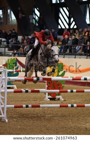 KAPOSVAR, HUNGARY - MARCH 15: Sandor Pinter Legenyei jumps with his horse (Caro Freddo) on the Masters Tournament International Jumping Competition, March 15, 2015 in Kaposvar, Hungary - stock photo