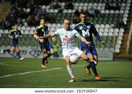 KAPOSVAR, HUNGARY - MARCH 16, 2014: Unidentified players in action at a Hungarian Championship soccer game - Kaposvar (white) vs Puskas Akademia (blue). - stock photo