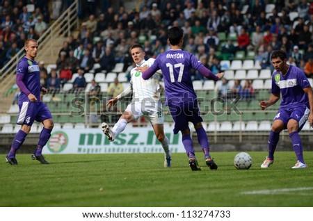 KAPOSVAR, HUNGARY - SEPTEMBER 14: Benjamin Balazs (in white) in action at a Hungarian National Championship soccer game- Kaposvar (white) vs Ujpest (purple) on September 14, 2012 in Kaposvar, Hungary. - stock photo