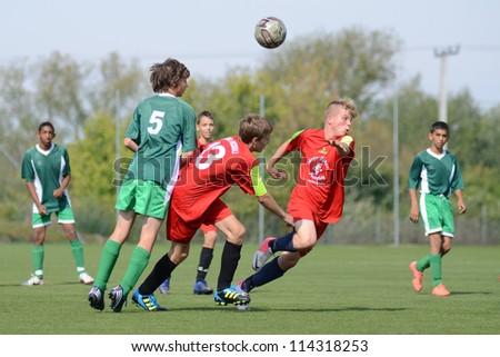 KAPOSVAR, HUNGARY - SEPTEMBER 22: Marton Kiss (green 5) in action at the Hungarian Championship under 15 game between Rakoczi (green) and Mezga FC (red) September 22, 2012 in Kaposvar, Hungary. - stock photo