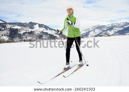 KAPRUN, AUSTRIA - FEBRUARY 2, 2015. A lady runs on skies in cross-country skiing area near Kaprun, Austria.   - stock photo