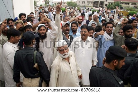KARACHI, PAKISTAN - AUG 29: Employees of electric supply company shout slogans in favor of their demands during protest demonstration at KESC head office on August 29, 2011 in Karachi, Pakistan. - stock photo