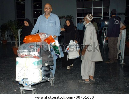 KARACHI, PAKISTAN - NOV 11: Hajj pilgrims come out from Hajj terminal at airport after their arrival on early morning in Karachi on Friday, November 11, 2011. - stock photo