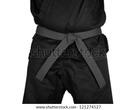 Karate grey belt tied around marital artists torso wearing black dojo GI's. - stock photo