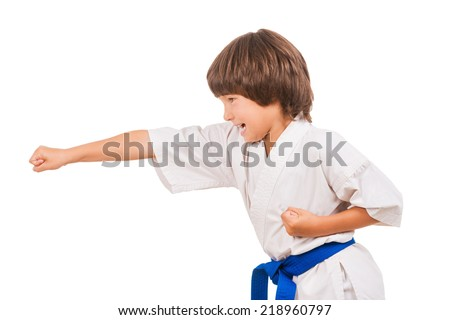 Karate kid. Side view of little boy doing martial arts moves while isolated on white background - stock photo