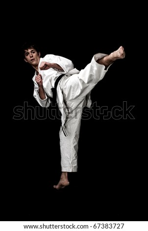 Karate male fighter young high contrast on black background - stock photo