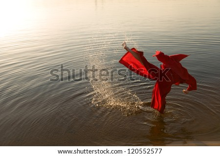 Karate monk wearing red hood at the lake shore - stock photo