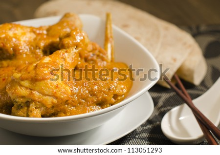 Kari Kapitan - Malaysian spicy chicken curry with coconut milk served with roti. Traditional Nyonya cuisine. Low key lighting. Close up. - stock photo