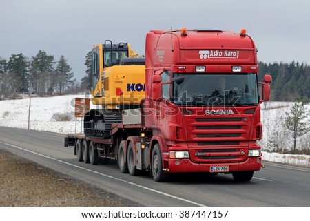 KARJAA, FINLAND - MARCH 5, 2016: Red Scania R500 hauls Komatsu PC 170LC excavator on lowboy trailer. The PC 170 LC uses CLSS hydraulic system that improves fuel efficiency. - stock photo
