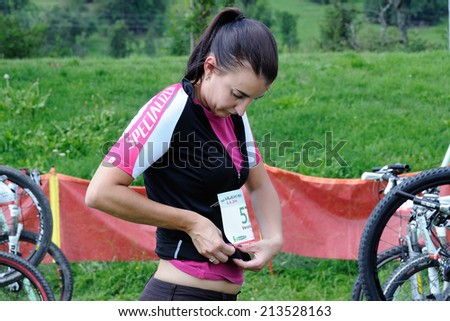 KAROLINKA, CZECH REPUBLIC - AUGUST 08, 2014: Female racer keeps her bib at the Valachia Man triathlon - stock photo