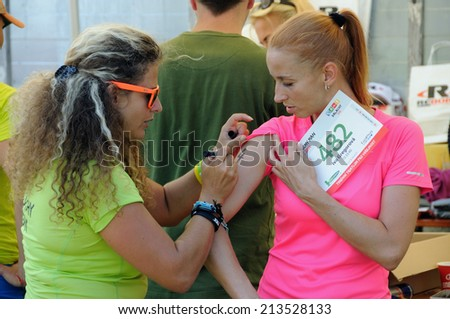 KAROLINKA, CZECH REPUBLIC - AUGUST 08, 2014: Female racer takes her start number at  the Valachia Man triathlon - stock photo