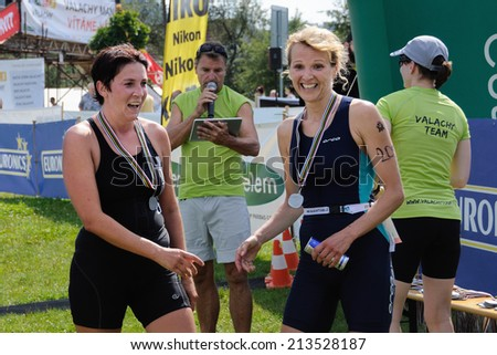 KAROLINKA, CZECH REPUBLIC - AUGUST 08, 2014: Female racers finish the Valachia Man triathlon - stock photo