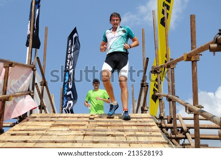 KAROLINKA, CZECH REPUBLIC - AUGUST 08, 2014: Male racer runs the Valachia Man triathlon - stock photo