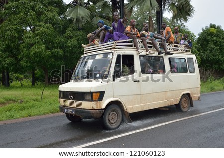 KARTIAK,SENEGAL-SEPT 18:people in the bus roof go to ritual of Boukoutt of Initiation ceremony on Sept 18,2012 in Kartiak,Senegal.The ceremony occurs every 30 years and celebrates boys becoming men - stock photo