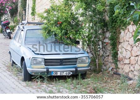 KAS, TURKEY, 29 APRIL, 2015: Retro car on the sidewalk under a bush - stock photo