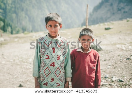 KASHMIR, INDIA - JUNE 29, 2014: Unidentified poor Indian beggar boy on street in Kashmir. Children of the early ages are often brought to the begging profession. - stock photo