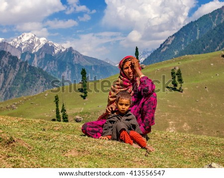 KASHMIR, INDIA - JUNE 29, 2014: Unidentified poor Indian beggar family on mountain in Kashmir. Children of the early ages are often brought to the begging profession. - stock photo