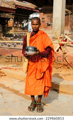 KATHMANDU, NEPAL-AUGUST 21: A buddhist monk standing in front of the tower of Hanuman Dhoka Square for alms on August 21, 2014 at Hanuman Dhoka Durbar, Kathmandu, Nepal.   - stock photo
