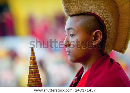 KATHMANDU, NEPAL - MARCH 25: Young Buddhist monk Karma, 9, carrying the Torma during Cham mystery at Shechen monastery on March 25, 2010 in Kathmandu, Nepal.  - stock photo
