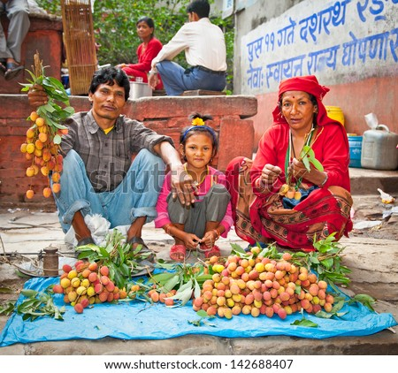 KATHMANDU, NEPAL - MAY 19: Family sell lychee fruits on a street market in Kathmandu on May 19, 2013. On United Nations list Nepal as one of the Least developed country in the world. - stock photo