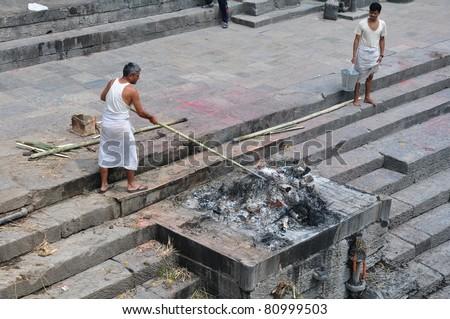 KATHMANDU, NEPAL - MAY 17: Hindu burning of a body at Pashupatinath temple on may 17, 2011 in Kathmandu, Nepal. It is traditional Hindu cremation ceremony. - stock photo