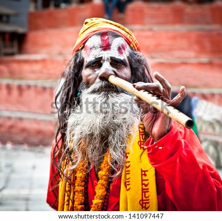 KATHMANDU,NEPAL-MAY 18: Sadhu play flute at Pashupatinath Temple in Kathmandu, Nepal on May 18, 2013. The two primary sectarian divisions in sadhu community are Shaiva sadhus and Vaishnava sadhus. - stock photo