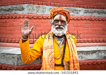 KATHMANDU, NEPAL - MAY 18: Shaiva sadhu seeks alms on the Pashupatinath Temple  on May 18, 2013 in Kathmandu, Nepal - stock photo