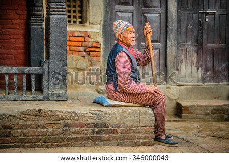 KATHMANDU, NEPAL - OCTOBER 21, 2015 : Elderly beggar with a walking stick sits in the street of Kathmandu - stock photo