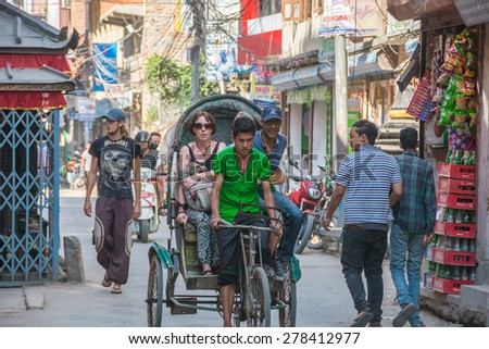 KATHMANDU, NEPAL - OCTOBER 07, 2014: Rickshaw with tourists in the back in Thamel area, Kathmandu.  - stock photo