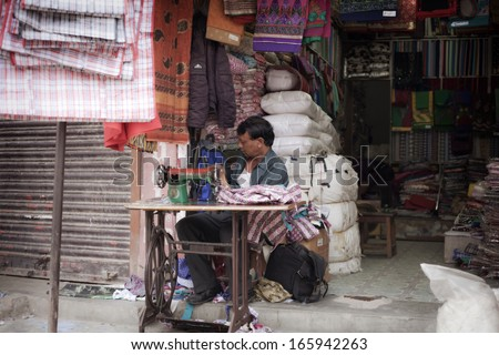 KATHMANDU - OCTOBER 2: man sewing in a small tailor shop, industrial sewing machine in l Kathmandu on October 2, 2013 in Kathmandu, Nepal. - stock photo