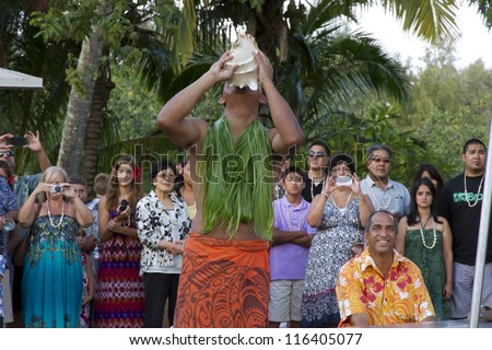 KAUAI, HAWAII - AUGUST 11: Aloha festival. Attractive young man in traditional Hawaiian dress plays seashell on August 11, 2012 in Lihue, Kauai - stock photo