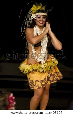 KAUAI, HAWAII - AUGUST 11: Aloha festival. Attractive young woman in traditional dress performs Hawaiian dance on August 11, 2012 in Lihue, Kauai. - stock photo