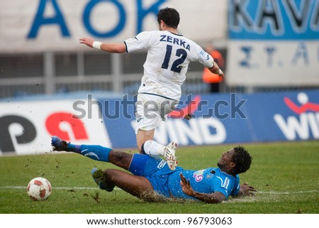 KAVALA, GREECE - JANUARY 23: Iraklis player Monsef Zerka (standing) fights for the ball with Kavala player Douglas Foureira (on the ground) during the Kavala vs Iraklis game at Kavala stadium on January 23, 2011 in Kavala, Greece - stock photo