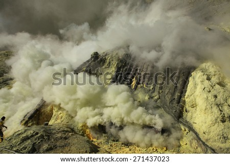 KAWAH IJEN, INDONESIA - AUGUST 8, 2011: Miner collects sulphur in the fumes of toxic volcanic gas at the sulphur mines in the crater of the active volcano of Kawah Ijen, East Java, Indonesia. - stock photo