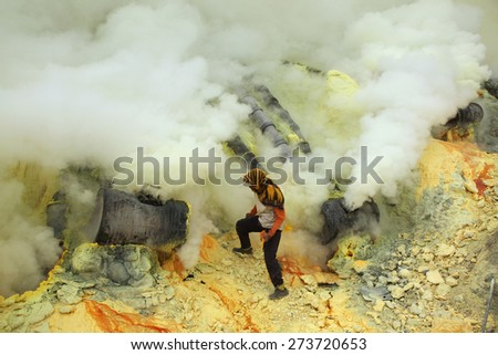 KAWAH IJEN, INDONESIA - AUGUST 10, 2011: Miner collects sulphur in the fumes of toxic volcanic gas at the sulphur mines in the crater of the active volcano of Kawah Ijen, East Java, Indonesia. - stock photo