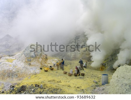 KAWAH IJEN,INDONESIA-JAN 10:Unidentified miners harvest raw sulphur from the crater of Kawah Ijen volcano in hazardous working environment with minimal protection on Jan10,2011 in Kawah Ijen - stock photo