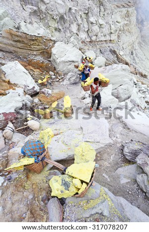 KAWAH IJEN, INDONESIA - JUNE 21: Unidentified people miner carry baskets with sulfur from the sulfur mines in the crater of the active volcano of Kawah Ijen on June 21, 2015 in East Java, Indonesia - stock photo