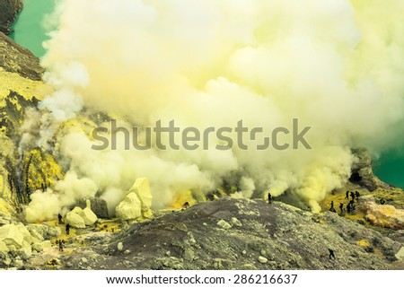 Kawah Ijen volcanic crater lake and toxic sulfur fume,workers extract sulfur from this smoky area and carry a-80-90 Kg.-basket full of sulfur on their shoulder and unload the baskets 3,5 Km away. - stock photo