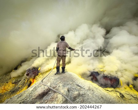 Kawah Ijen Volcano, East Java, Indonesia - May 25, 2013: Sulfur miner spraying water onto pipes inside the crater of Kawah Ijen volcano in East Java, Indonesia. - stock photo