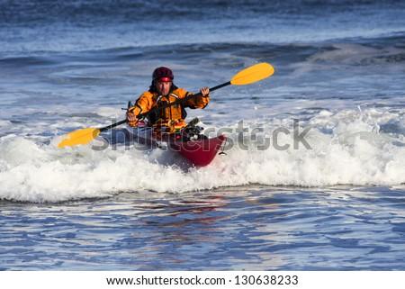 Kayak man over big wave on rough sea of Nova Scotia coast, Canada - stock photo