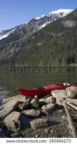 Kayak on a rocky beach on Chilkoot Lake in Southeast Alaska. - stock photo