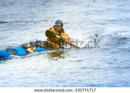 Kayak surfer on rough sea  by cloudy day on Nova Scotia coastlines, Canada - stock photo