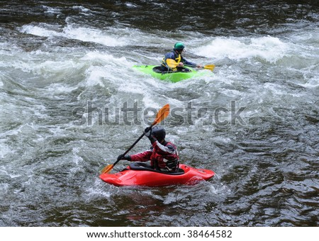 Kayakers, playing in the rapids - stock photo
